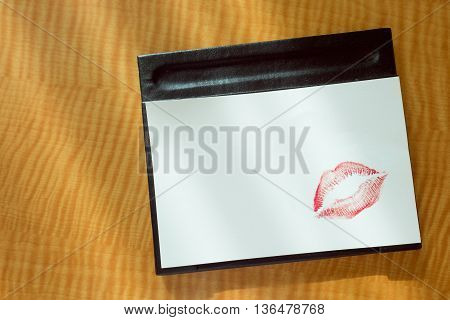 Sexy girl Red lips kiss on blank white note paper on bed stand table in the morning light.  romantic message from couple.