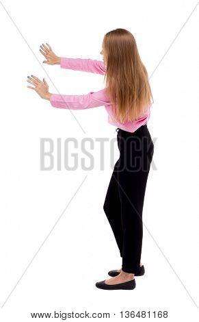 back view of business woman pushes wall.   Blond girl in a green skirt pushing something heavy right. girl office worker in black trousers shoves something in front of him.