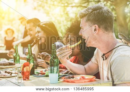 Multi ethnic people group enjoying grill meal at backyard barbecue meeting - Young friends having bbq party - Lunch and dinner concept outdoors - Soft focus on blond guy - Vintage retro filter