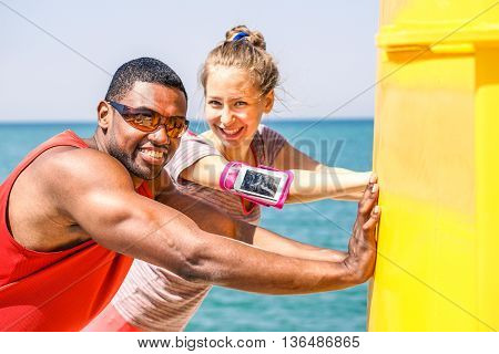 Multiracial friends making stretching after jogging next sea - Young people smiling and relaxing before a training session - Healthy lifestyle and sport concept - Soft warm saturated filter
