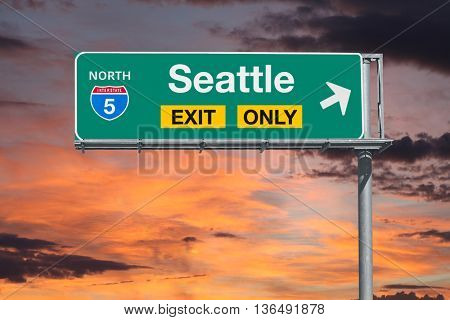 Seattle exit only 5 freeway sign with sunrise sky.