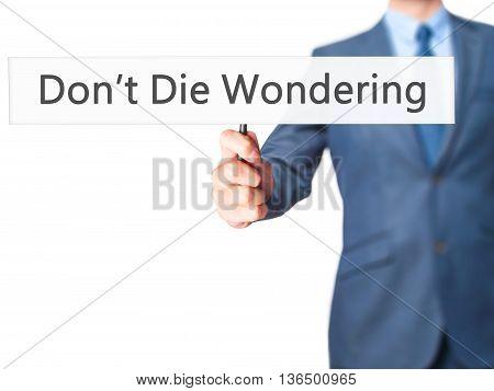 Don't Die Wondering - Businessman Hand Holding Sign