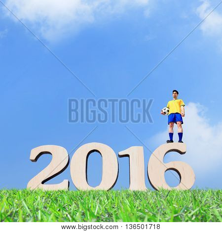 Brazilian soccer football player man holding ball and stand on the 2016 text with blue sky