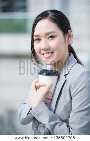 business woman smile and hold coffee cup with office background asian shot in Hong Kong