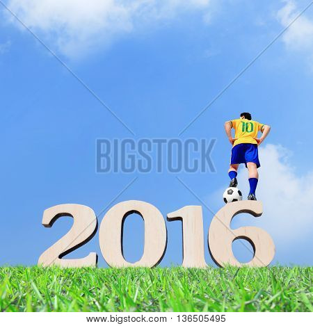Brazilian soccer player man striking the ball and stand on the 2016 text with blue sky