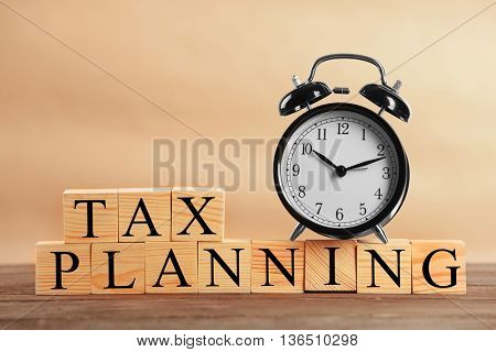 Tax concept with wooden cubes and alarm clock on light background