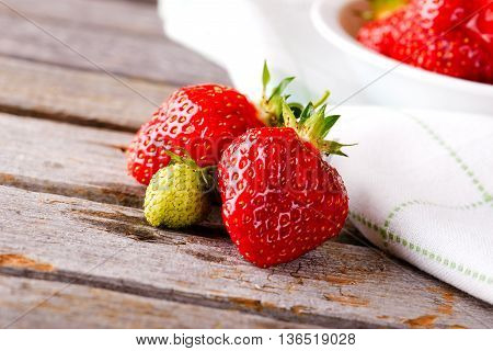 Green Unripe Strawberry With Red Ones Next To Bowl