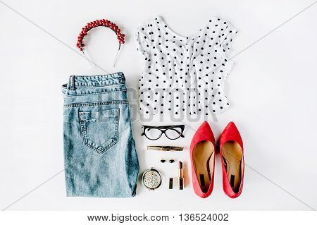 flat lay feminini clothes and accessories collage with shirt jeans glasses mascara lipstick red high heel shoes earrings and hoop on white background.