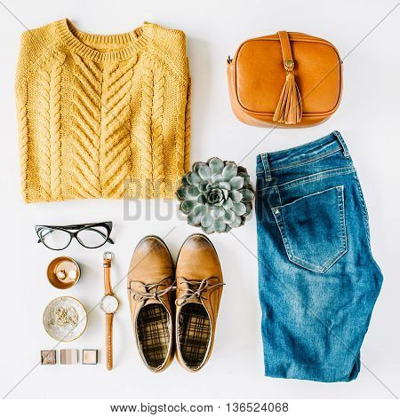 flat lay feminini clothes and accessories collage with brown cardigan jeans glasses watch earrings purse boots and succulent on white background.