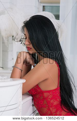 portrait of stunning yong woman in lace underwear in white bedroom sitting and looking down and thinking