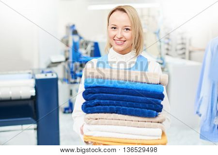 Girl worker holding a Laundry service clean towels and smiling