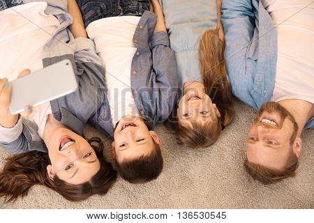 Happy family having selfie on the floor