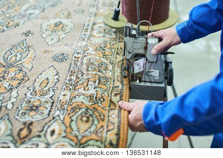 Hand Laundry worker sew a carpet on the automatic sewing machine at the dry cleaners