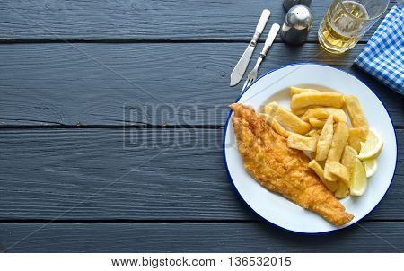 Fish and chips on a wooden table with space