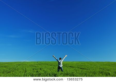 Young Man Outstretched Arms In Green Field Against The Blue Sky