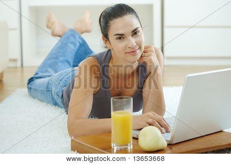 Happy Woman auf Boden zu Hause liegen und arbeiten auf Laptop-Computer, lächelnd.