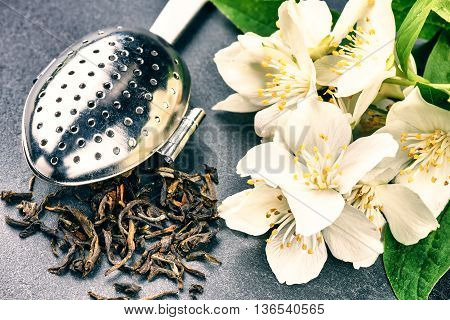 Tea infuser spoon with dry green tea leaves and fresh jasmine flowers