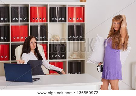 Sleepy woman in a nightgown with alarm clock in a hand stands in the office of the the chief. Being late for work.