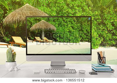Conceptual image of a work space and computer desktop with sunbeds on beautiful beach in resort