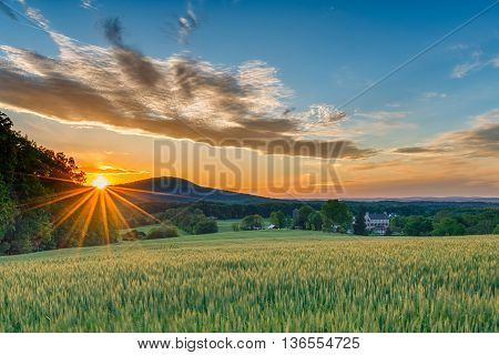 A perfect Spring day ends as the sun sets and sprays warm golden light over a beautiful farm with fields sprouting a stone house and mountain ridges in the background.