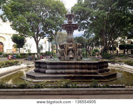 ANTIGUA GUATEMALA - SEPTEMBER 30 2015: Ancient fountain in the central square of Antigua Guatemala's former capital
