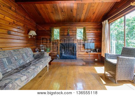 Cozy interior of a rustic log cabin with a fireplace.