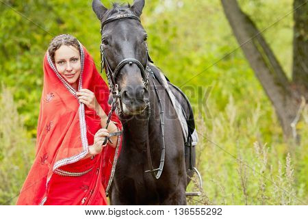 Woman with curly hair in red clothes and chestnut horse in park.