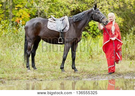 Blonde woman with plait in red clothes stands with horse in park near water.