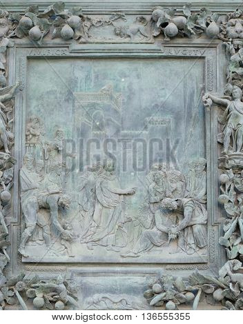 PISA, ITALY - JUNE 06, 2015: The payment of the tribute, sculpture work from Giambologna's school, the left portal panel of the Cathedral St. Mary of the Assumption in Pisa, Italy on June 06, 2015