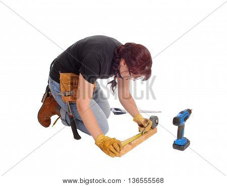 A middle age woman kneeling on the floor and working with some tools measuring isolated for white background.