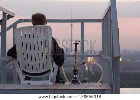 Young man smoking hookah sitting on armchair on highrise roof at sunset, rear view.