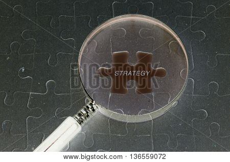 Business concept : Jigsaw puzzle background and magnifying glass and copyspace area with STRATEGY word