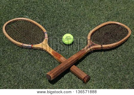NEW YORK - JUNE 30, 2016:Vintage Tennis rackets and Slazenger Wimbledon Tennis Ball on grass tennis court. Slazenger Wimbledon Tennis Ball exclusively used and endorsed by The Championships, Wimbledon