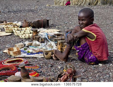 LAKE TURKANA KENYA-JANUARY 12: Unidentified El molo child sells traditional souvenirs January 12 2013 near lake Turkana Kenya. The El molo are one of the disappearing tribes of Africa.