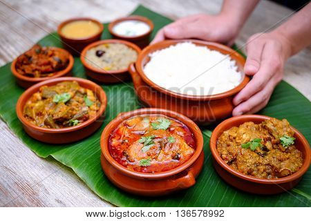 Indian meal with braised pork curry and plain rice on banana leaf tray