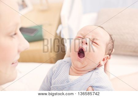 Newborn baby yawning in his mothers arms