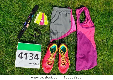 Running shoes, marathon race bib (number), runners gear and energy gels on grass background, sport, fitness and healthy lifestyle concept poster