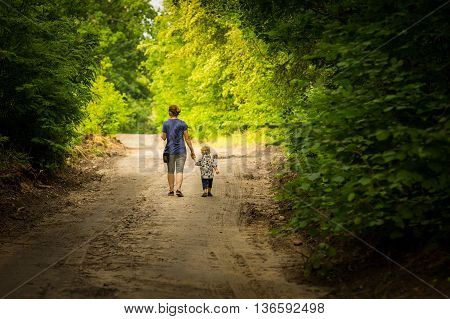 Mother And Child Walking By Forest Path