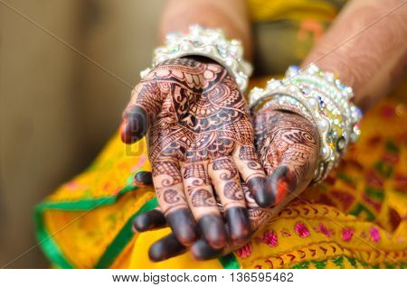 Close up photo of Indian bride's palms with henna tattoo and white bangles