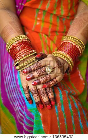 Indian woman's hand with henna tattoo and traditional red colored Indian bangles