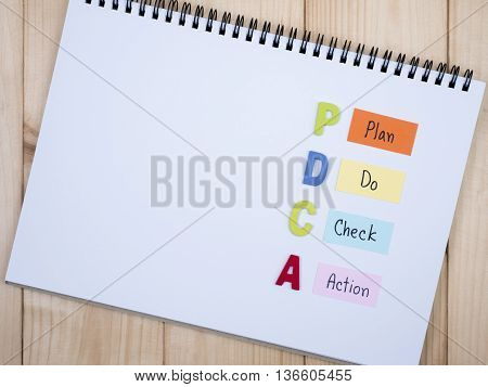 Wooden word PDCA and handwriting Plan Do Check Action) on notebook in wood background (Business Concept)