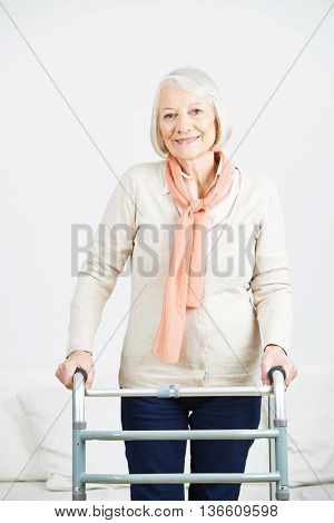 Smiling old woman standing with walker at home