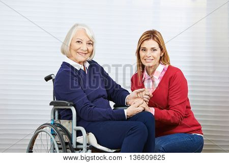 Young and old woman holdind hands together in a nursing home