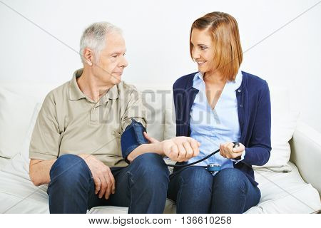 Woman doing blood pressure monitoring for patient in nursing home