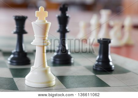 White chess king alone surrounded by the opposite pieces selective focus on white chess king piece poster