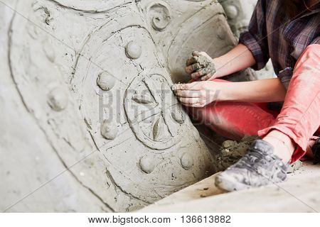 Closeup female sculptor works with fragment of clay sculpture in workshop.