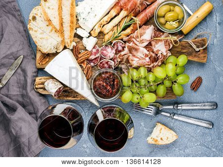 Cheese and meat appetizer selection. Prosciutto di Parma, salami, bread sticks, baguette slices, olives, sun-dried tomatoes, grapes and nutson rustic wooden board over grey concrete textured backdrop, top view