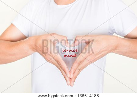 heart shape hands on left side chest of a man in white shirt with words - service mind