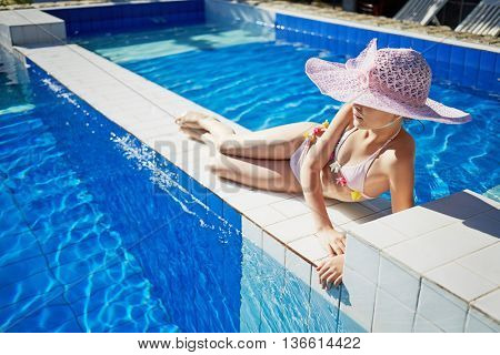 Girl in swimsuit and wide-brimmed hat tans lying on partition between pools.