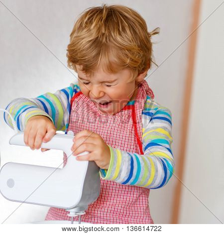 Cute funny blond toddler kid boy baking apple cake and muffins in domestic kitchen. Happy child having fun with working with mixer, flour, eggs and fruits at home.